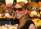 Mariah Carey shows cleavage in low-cut black top and her booty in tight jeans at a Tokyo shopping mall to promote her latest album EMC2 in Japan